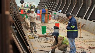 Construction workers for the Mexican contracting company Coconao work on a segment of the new rail bridge that stands over the Rio Grande.