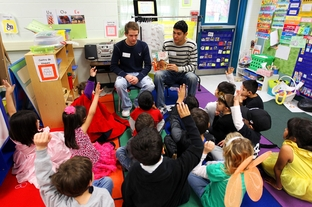 National Honor students Zach Calkins and Aaron Gonzales, seniors at Brandeis High School, read to kindergarten students in a crowded classroom at Wanke Elementary School in San Antonio on March 9, 2012.