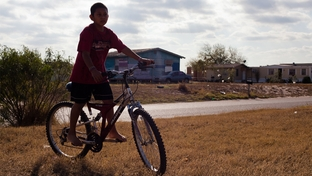 A child rides his bike in the Del Mar Heights colonia in the Rio Grande Valley.