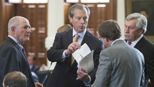 Lt. Governor David Dewhurst (c) goes over legislation with colleagues on the Senate floor April 18, 2011