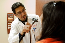 Dr. Xavier Muñoz treats a patient in El Paso. Muñoz agreed to treat low-income, underinsured patients in return for having his medical school bill repaid — a program that could be eliminated through state budget cuts.