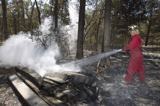 Fireman Bret Deakins of Quinlan puts out a hot spot in a wood pile in Bastrop County on September 9, 2011.