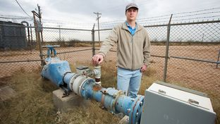Kyle Krueger, a staff engineer with the Colorado River Municipal Water District, stands next to an older water well on land acquired through state financing near Wickett, Texas.