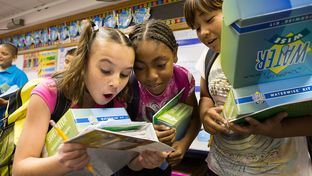 Three students at Bayless Elementary in Lubbock, Texas, consult a water usage chart after being presented with water conservation information and Waterwise kits by the High Plains Underground Water District.
