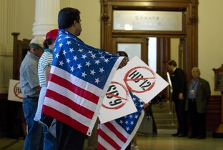 "Protesters with American flags line the hallway outside the Senate chamber protesting HB12 the so-called ""sanctuary cities"" bill on May 25, 2011."