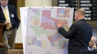 State Rep. John Kuempel, R-Seguin, looks through redistricting maps on display during debate on the House floor on June 14, 2011.