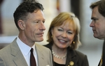 Texas singer Lyle Lovett (l) talks with Rep. Myra Crownover (c) and Rep. Dan Branch (l) during an appearance on the House floor on March 31, 2011.  Lovett is advocating a bill authorizing slot machines at Texas racetracks.