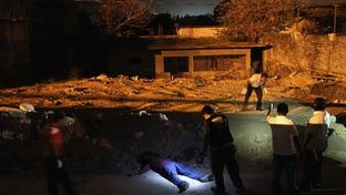 A forensics team inspects the body of a man killed in a suspected drug-related execution along the path where he was shot on March 1, 2012 in Acapulco, Mexico.