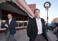 Gov. Rick Perry walking down Adams Street in Creston, Iowa, with Department of Public Safety trooper Chris Brannen after speaking at a presidential campaign event on Dec. 27, 2011.