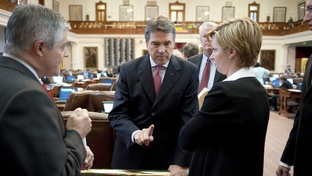 Texas Gov. Rick Perry (c) visits with House members to discuss the state budget issues at the back railing on May 19, 2011.