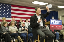 Rick Perry grins as he holds up a paper that symbolizes his flat tax plan during a stop in Osceola, Iowa on December 27, 2011.