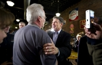 Texas Governor Rick Perry greets an Iowa voter at the Smokey Row Coffee Shop in Oskaloosa on December 28, 2011.