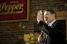 Rick Perry stands in the spotlight while answering a question at the Smokey Row Coffee House in Oskaloosa, Iowa on December 28, 2011.