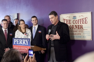 Republican candidate Rick Perry, right, speaks to Washington, Iowa voters on December 29, 2011.