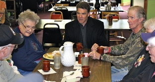 Rick Perry sits down to have coffee with people at Sisters Main Street Cafe in Spencer Iowa.