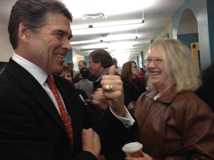 Rick Perry speaks with a member of the Point of Faith church in Waukee Iowa.