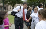 Governor Rick Perry (c) holds the hand of teacher Joan Stein as he greets schoolkids outside the Texas Capitol shortly after lunch on April 19, 2011.