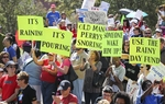 Marchers with signs criticize Governor Perry's stance on school funding cuts in the Save Our Schools march to the Capitol on March 12, 2011.