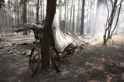 The remains of a mobile home lie smoldering in a small subvision east of Bastrop where the wildfire went through earlier in the day on September 6, 2011.
