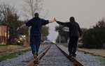 James and his adoptive son walk along railroad tracks at dusk in Addison on January 30, 2011. The son, who is 15, is on a state registry of people who abuse children.