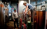 Amos Lowe, a brewer and Kim Mizner prepare fermentation tanks at Uncle Billy's Brew & Que in Austin.