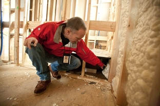Douglas McAffe inspecting the insulation of a house in central Austin.