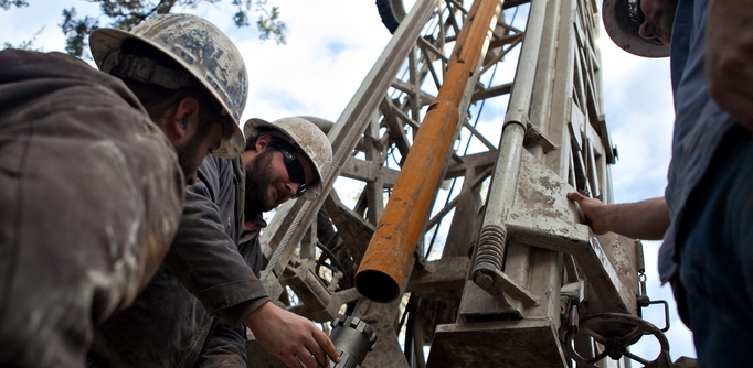Workers with Bee Cave Drilling install a jackhammer bit on the drilling rig while putting in a water well on a private lot in Spicewood, Texas on February 6, 2012.