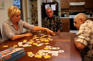 Health care assistant Crystal Kreig plays a card game with Steve Parker (center) and Eulalio Alvarada (right) at a group home operated by D&S Residential, Inc. Companies like D&S used to handle case management for their clients, but a budget change sent that responsibility to local Mental Retardation Authorities.