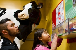 Sophia Lara and her father Ricardo look at a display in the dairy processing plant at the Austin Children's Museum.