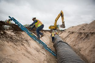 Water pipeline crew members prepare for the laying of the next section of the 60-mile-long chain running near Eden, Texas.