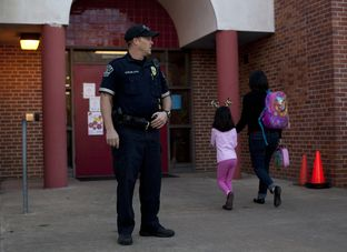 Austin Police Officer Cory Ehrler monitors the entrance to Ridgetop Elementary School after classes start on the Monday following the Sandy Hook Elementary School shooting. As the 83rd legislative session approaches, Texas lawmakers are considering making firearms more available to teachers and other school personnel.