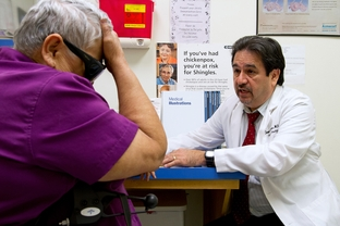 Dr. Javier Saenz with a patient, Elena Chavez, 73. Chavez is part of the 50 percent of patients Saenz sees who draw from both Medicare and Medicaid.