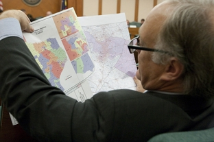 State Sen. Kirk Watson, D-Austin, takes a look at redistricting maps at the Senate Select Committee on Redistricting on May 13, 2011.