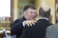 State Sen. Tommy Williams, R-The Woodlands, speaks to an aide after the Senate session on May 16, 2011.