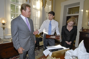 Texas Governor Rick Perry (c) and wife Anita Perry (r) greet California Governor Arnold Schwarzenegger at the Governor's Mansion on August 24, 2006.