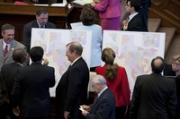 Legislators review redistricting maps on the House floor.
