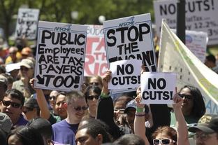 Pro-union protesters hold signs decrying budget cuts at the Texas Capitol on April 6, 2011.