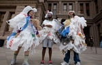 Activists from Texas Campaign for the Environment demonstrate at the Texas Capitol covered with single-use bags to protest bills that would limit the ability of cities to ban disposable bags.