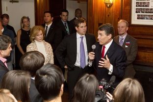 Rick Perry, r, speaks at a Dartmouth fraternity house as wife Anita Perry, r, and son Griffin, c, listen following the Dartmouth Debates on October 11, 2011.