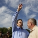 Governor Rick Perry waves to a guest at the Iowa State Fair in Des Moines while walking with Secretary of Agriculture Bill Northey (r) on August 15, 2011.