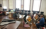 Jeremy Coleman teaches Albert Torres, 16, and Auggie Guerrero, 18, how to play guitar at Austin Can! Academy.