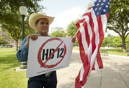 "Hispanic male holds American flag and sign showing his opposition to HB12 the ""sanctuary city"" bill on Capitol grounds May 23rd, 2011"