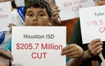 Young Hispanic student from Houston holds with sign indicating budget cut amount to school district during press conference on June 6th, 2011