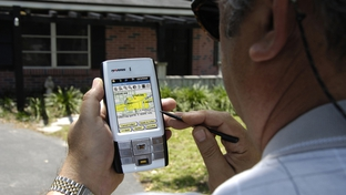 A U.S. Census Bureau worker confirms addresses with a hand-held device.