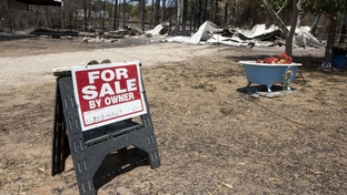 A For Sale sign in front of a burned-down house on Sept. 13, 2011, after the wildfires in Bastrop County.
