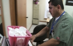 A worker at a Mission clinic carries out a box of birth control containers.