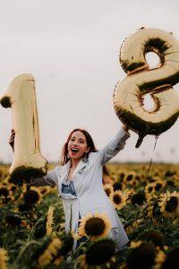 Vanessa holding 18 balloons