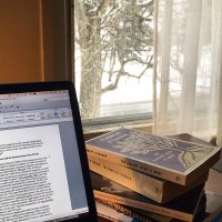 Picture of desk with computer and books with snow falling outside the window in the background