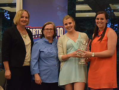 NE-10 Commissioner Julie Ruppert (left) presents the 2014-15 Presidents' Cup to Cindy MacDonald, Interim Director of Athletics, and student-athletes Analise Kump and Meaghan Martin. Kump (women's tennis) and Martin (volleyball) were both part of the Skyhawks seven NE-10 Championships this year! (PHOTO COURTESY of the Northeast-10)