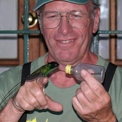 Man wiht  hummingbird on his finger drinking from a bottle.